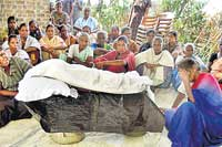 The weeping mother and villagers beside the coffin of the child.
