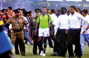 Referee Irshad Cader being escorted out of the Royal College Sports Complex field by Police personnel after the Bradby first leg last weekend. 		    - Pic by Mangala Weerasekara