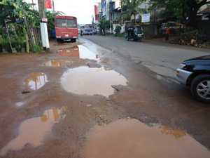 Status of road after newly laid asphalt. (Top left)No sidewalk. (Top right) Asphalt peeling off.