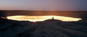 On the edge: Two people stand and look into the burning hole, which has become known as 'The Door to Hell'