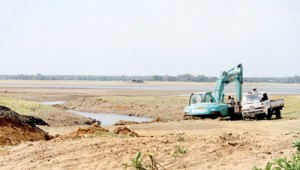 Backhoes at work: Digging up trenches so that the water below the sluice gates of the Parakrama Samudraya can be used.