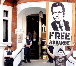 A protestor holds a poster of Wikileaks founder Julian Assange outside Ecuador's embassy in London on Friday. Reuters