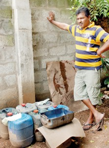 Karunarathna Sunil stands beside the contaminated fuel he had to empty from his bus. Pic by M.D. Nissanka