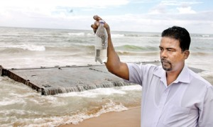 A Marine scientist testing the sea water in  Bambalapitiya. On the background is a piece from the broken ship. Pic by Indika Handuwala