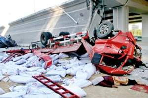 Collapse: Huge trucks lie on their side after being thrown off the Yangmingtan Bridge after it collapsed in Harbin in Heilongjiang province, north east China. The body of a driver lies next to one of the overturned trucks