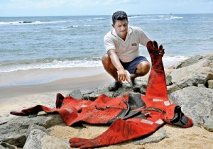 An oil-soaked diver's kit washed ashore on the Negobom beach yesterday. Pic by Susantha Liyanawatte