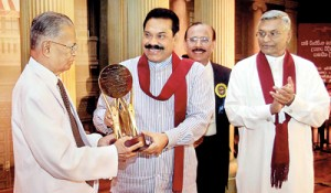 President Mahinda Rajapaksa presents a memento to Sam Wijesinhe at the ceremony yesterday while Speaker Chamal Rajapaksa looks on. Pic by Sudath Silva