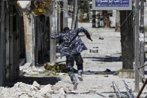 A Free Syrian Army fighter runs away to take cover from the exchange fire with regime forces in  Aleppo (REUTERS)