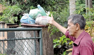 E. Karunarathne from Kotte points to the garbage collected on his gate post. Pix by Indika Handuwala