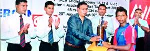 Under 15 winning captain, Avisha Wilwarachchi on right, receives the champions trophy from Gyruka Perusinghe.