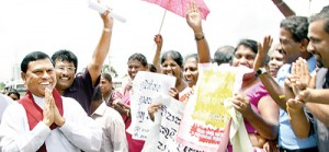 All smiles: Minister Basil Rajapaksa greets a group of people at the parliament round-about holding up posters in support of the Divineguma Bill