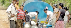 A sight for relieved eyes: Villagers in a remote corner of the Dimbulagala  Division fill up pots and pans from the weekly bowser