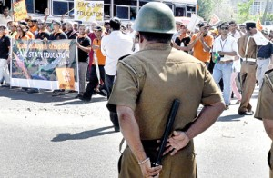 Ready for action: A policeman on full alert as  protestors converge on Hyde Park in Colombo on Friday. Pic by Mangala Weerasekera