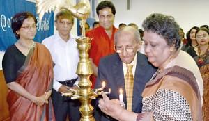 Sumithra Peiris and Dr. Lester James Peiris lighting the traditional oil lamp