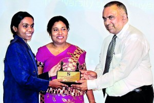 Executive Director Marketing of Ceylon Business Appliances, Johanne De Zilva, hands over the felicitation trophy to Woman Fide Master (WFM) Ms. Pramodya Senanayake.  Olympiad Gold Medalist Mrs. Suneetha Wijesuriya, Chairperson of Lanka Chess Foundation, who organized the programme at Colombo Hilton to commemorate the 20th year of the Chess Olympiad Gold Medal  is also in the picture.