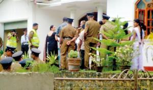 Police officers investigating the latest killing to shock Kahawatte. Photo: Lasantha Niroshana