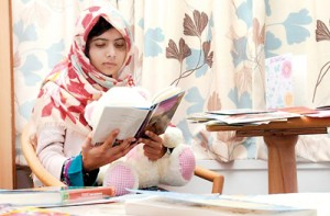 Malala Yousufzai reads a book as she recuperates at the The Queen Elizabeth Hospital (Reuters)