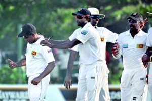 Spinner Rangana Herath (left) who took a five-for is congratulated by speedster Shaminda Eranga, who made the initial breakthrough after Sri Lanka bundled out New Zealand for 221. Pics by Amila Gamage
