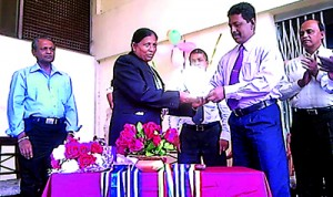 Deputy Post Master General Rajitha Ranasinghe presents her with a trophy