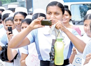 Nurses staged a token strike on Thursday and held demonstrations to protest over the Government's failure to meet their demands including overtime payments and risk allowances. Some nurses are seen using their cameras and phones to take pictures of their own protest held opposite the Health Ministry in Colombo. Pic by  Susantha Liyanawatte.