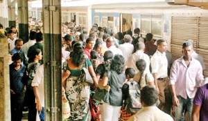 Passengers struggle to board a train at Sri Lanka's  main station at Fort