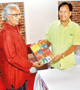 The author hands over the book to chief guest Minister Sarath Amunugama at the launch on Thursday. Pic by Managala Weerasekera