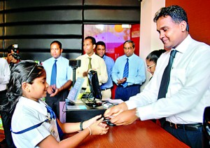 Mr. Rajiv Gunasena, Deputy Managing Director - M. D. Gunasena hands over a Loyalty Card to a student of Visakha Vidyala Colombo which was the first school to receive the Loyalty Membership