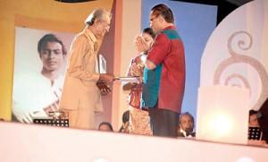 Ivor receiving a memento from  Sunil Santha's son Lanka