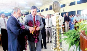Prof. Sarath Amunugama, Vice Chancellor of the Kelaniya University (left) and Prof. Malik Peiris lighting  the traditional oil lamp at the launch of the 13th Annual Research Symposium
