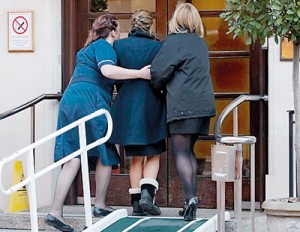 Distraught: Nurses at the hospital head inside while clinging to each other after hearing the news