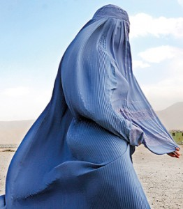 An Afghan burqa clad pedestrian walks as a girl looks on in the old city of Herat (AFP)