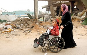 Palestinian children with special needs walk past buildings destroyed during the Gaza-Israeli conflict during a demonstration on the occasion of the UN International Day of People with Disability, on December 4, 2012 in Gaza City ( AFP)