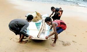 Children drag their  boat ashore