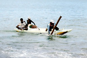 A group of men bring  their boat ashore