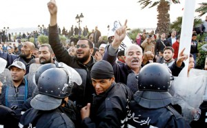 Pro-government Islamists clash near riot police during a demonstration against labour union UGTT that called for a general strike and downfall of the government led by the Islamist Ennahda party at Kasba in Tunis on December 4. Reuters