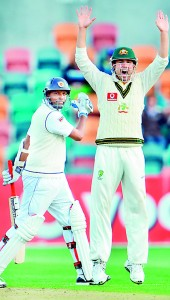 Thilan Samaraweera walks off after being dismissed as Ed Cowan celebrates on the second day of the first cricket Test match against Australia in Hobart - AFP
