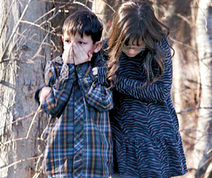 Young children wait outside Sandy Hook Elementary School after the shooting (REUTERS)