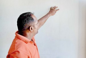 A resident shows the crack on a wall in his house