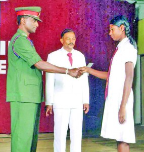 A prefect receives his badge from the chief guest Brigadier Ariyasinghe