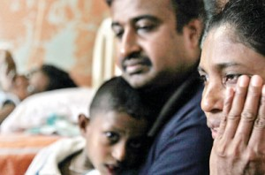 The picture says it all: Why us, asks Nilanthi as she sits at the bedside of her daughter Tharindi (above, inset) at the LRH along with her husband and little son, who is also showing signs of the disease.