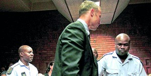 South African 'Blade Runner' Oscar Pistorius (C) is escorted by police during his court appearance in Pretoria February 15, 2013. -REUTERS