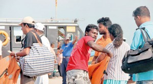 All aboard: A Navy personnel calls out to passengers  at the Kurikattuwan jetty