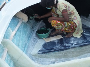 Tharmalingam Tharnam, crouched and painting the front inside of a fibre-glass boat under construction; The boats manufactured at  Jayapuram, Kilinochchi lined up for distribution to fishermen of Poonakari