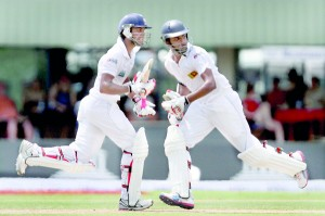 Dinesh Chandimal (L) and Lahiru Thirimanne (R) cross over for runs during their marathon unbroken partnership of 203 runs for the fifth wicket. Both Chandimal and Thirimanne went on to hit their debut Test tons on the second day against Bangladesh at Galle.                           - Pic by Shantha Ratnayake