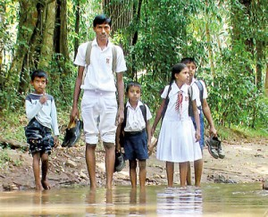 No roads, students must roll up their uniforms and remove footwear to get to school