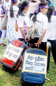"""The focus of International Women's Day activities in Sri Lanka was on the plight of nearly one million women going through severe hardship in West Asian countries. The Freedom for Women Movement and other groups staged a protest march from Hyde Park to Green Path, Colombo, carrying housemaid's travelling bags with the cry """"Duleeka then, Rizana yesterday and who's next"""".  Pic by M.D. Nissanka"""