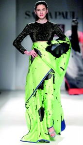 Model walks in a neon green designer saree with black printed work by Satya Paul during the Wills Lifestyle India fashion week (Reuters)