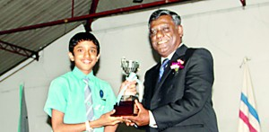 Lyceum Wattala Scrabble captain Migara Jayasinghe receiving the Overall Champion Trophy from the chief guest Wimal Fernando, the President of SLSL.