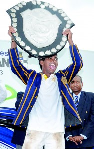 An elated Devind Pathmanathan holds aloft the D.S Senanayake Shield after receiving it from chief guest P.L.D. Kariyawasam -- the former Thomian skipper.