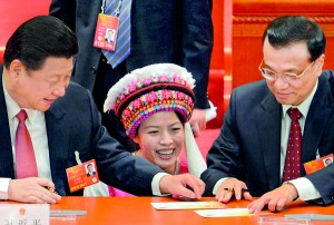 An ethnic delegate (C) gets the newly elected Chinese President Xi Jinping (L) and the newly elected Premier Li Keqiang (R) to sign an  autograph during the 12th National People's Congress (NPC) in the Great Hall of the People in Beijing on March 14. AFP